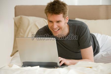 man using laptop on bed