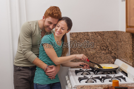 young man in kitchen arms around