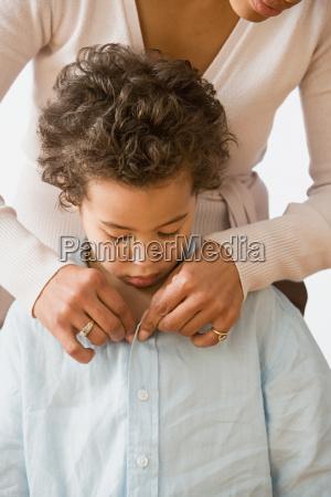 mother fastening boys shirt