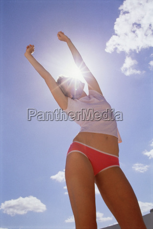 woman stretching in sunlight