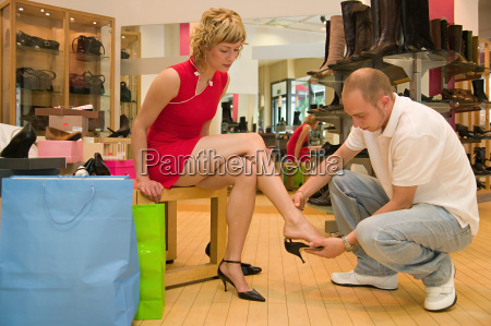 man, helping, girlfriend, try, on, shoes - 18878046
