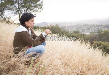 young woman crouching on grassy hill