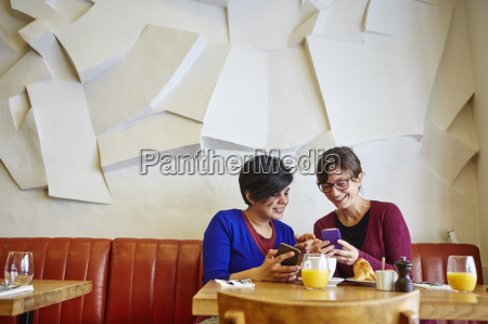 two adult female friends reading smartphone