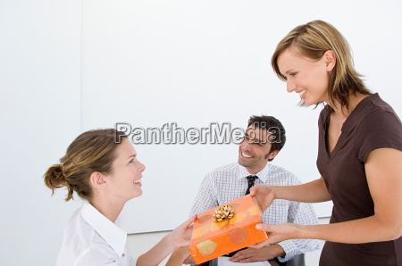 woman giving present to colleague