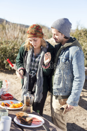 young couple preparing food standing beside