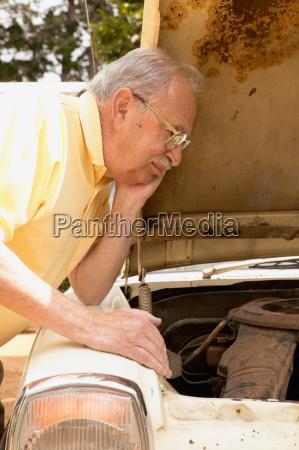 senior man looking at car engine