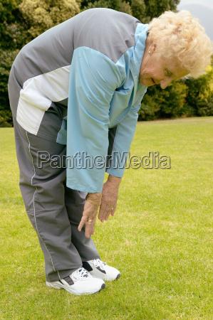 a senior woman stretching