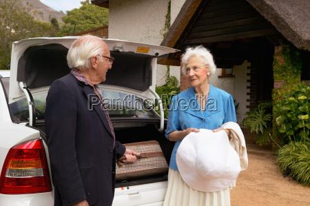 senior couple arriving by car