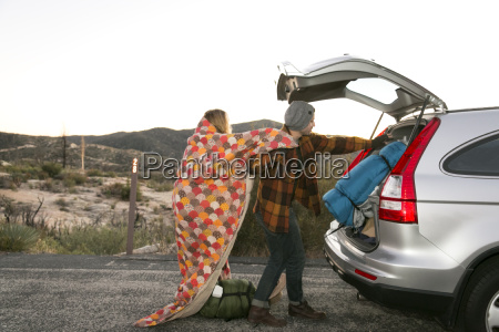 young couple putting camping equipment in
