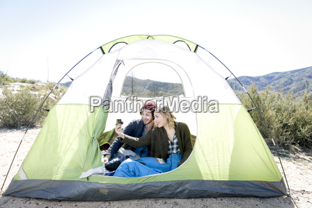 young couple sitting in tent taking