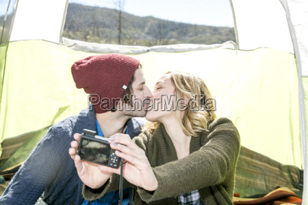 young couple sitting in tent kissing