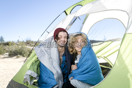 young couple sitting in tent wrapped
