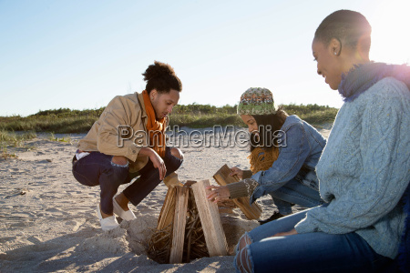 three friends on beach preparing camp