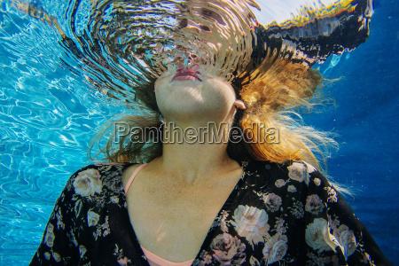 young woman underwater breaking through water