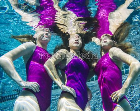 three female swimmers underwater hands on
