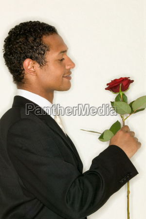 bridegroom holding a red rose