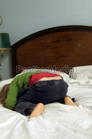 young girl lying on bed