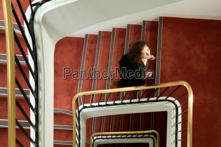 businesswoman walking up a spiral stairway