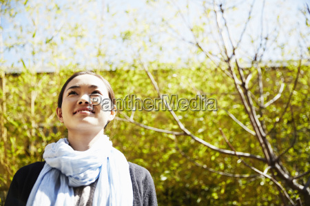 young woman wearing scarf looking up