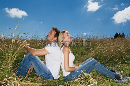 couple in a field sitting back