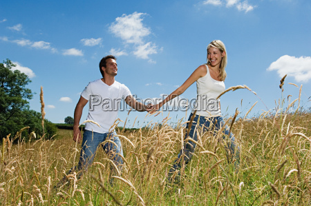 couple walking through field