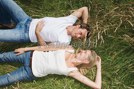 young couple lying in a field