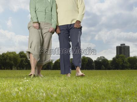 elderly couple walking bare foot in
