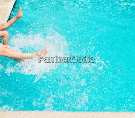 legs splashing water in swimming pool