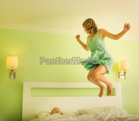 mother jumping on bed to wake