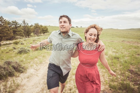 young couple running on hilltop track
