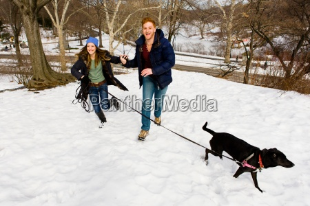 young couple running with dog in