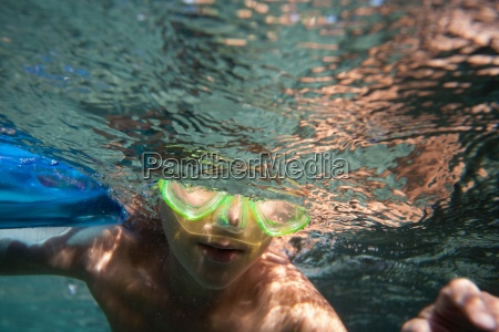 underwater view of boy wearing goggles