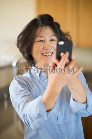 mature woman taking selfie indoors