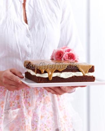 woman holding chocolate sponge coffee cake