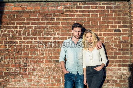 couple leaning against brick wall looking