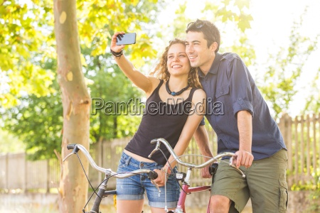 young couple with bicycle taking selfie