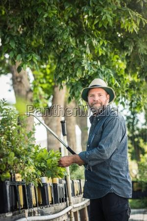 portrait of scientist spraying plants at