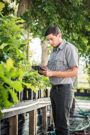 scientist updating digital tablet at plant