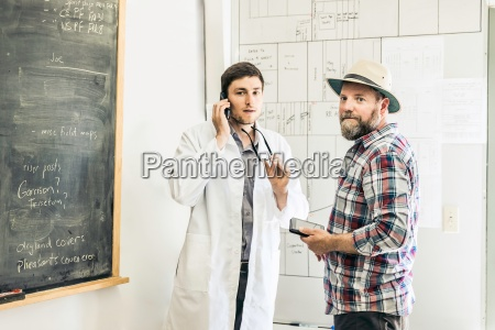 scientists talking on smartphone whilst planning