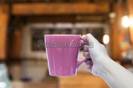 frau hand haelt kaffeetasse im cafe