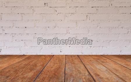 tischplatte aus holz mit backsteinwand