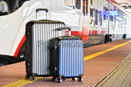 zwei plastik reisekoffer auf der bahnstrecke