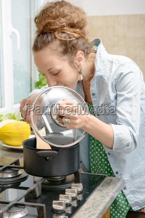 junge frau kochen abendessen in der