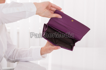persons hand holding empty purse