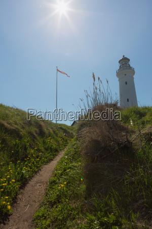 leuchtturm in den duenen im sommer