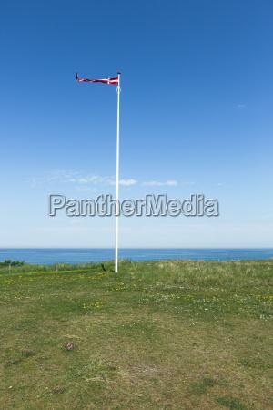 daenische flagge im wind vor blauem