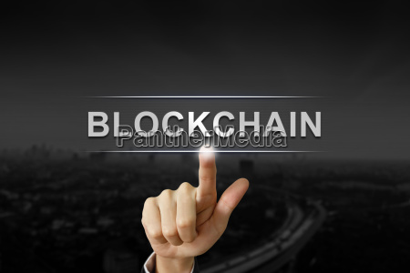 business hand pushing blockchain button on