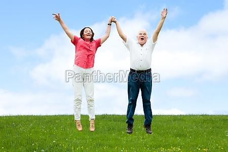 senior couple jumping on field