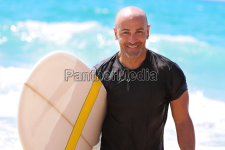 handsome man with surfboard