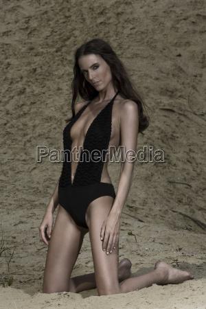 frau mit schwarzem badeanzug im sand